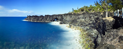 Cliffs on Reunion island. Scenic view of volcanic cliffs receding on Reunion island with blue sea and sky background royalty free stock photo