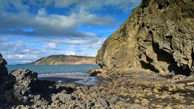 Cliffs and rock formations along black sand Whatipu Beach in Huia Stock Photos
