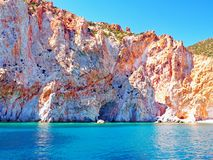 The cliffs and rock formations of Polyaigos, an island of the Greek Cyclades. Fantastic cliffs and rock formations rise from the crystal blue sea on Polyaigos stock photography