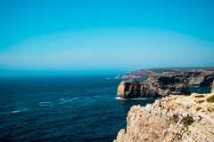 Cliffs on rocky coastline with blue sky Stock Photos