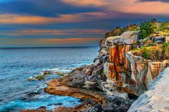 Cliffs and rough sea at sunset. Cliffs and rough sea under the orange sky at sunset. Photo is taken near Watsons Bay, Australia royalty free stock photo