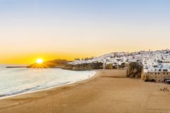 Cliffs, sandy beach and white architecture of Albufeira, Algarve. Sunset over beautiful cliffs between sandy beach and white architecture of Albufeira, Algarve Royalty Free Stock Image