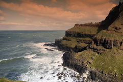 Cliffs by sea. Scenic view of cliffs on coastline with rocks in ocean stock images