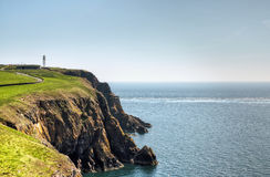 Cliffs and sea on the Mull of Galloway. View of a lighthouse on the cliffs jutting into the sea on the Mull of Galloway, South West Scotland on a summer day Royalty Free Stock Photography