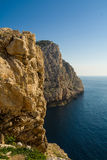 Cliffs and the sea. Sardinia. Blue sea and yellow rocks Stock Images