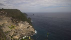 Cliffs, sea and waves at Nusa Penida, Bali, Indonesia. Seascape, rocky coast, ocean, blue sea, waves, Nusa Penida, Indonesia. Ocean with waves and rocky cliff Stock Image