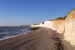 Cliffs - Seven Sisters. Cliffs on south coast of England near Birlin Gap (Seven Sisters); white cliffs on brown sand beach and ocean waves rolling in Stock Image