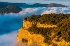 Cliffs in the Tavertet abyss covered with fog at dawn in the Col stock photography