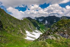 Cliffs in the valley of Fagaras mountains. Lovely summer scenery on a cloudy day. spots of snow on grassy hillside. beautiful landscape of Romania Stock Photo