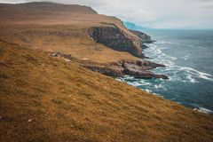Cliffs and the village on the island of Mykines, Faroe