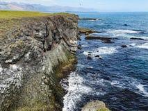 Cliffs washed by waves near gatklettur arch rock in snaefellsjok royalty free stock image