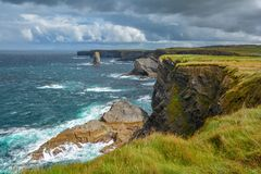 Cliffs and waves near Kilkee, County Clare, Ireland. Kilkee is a small coastal town in County Clare, Ireland. It is in the parish of Kilkee, formerly Kilfearagh Stock Photos
