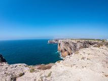 Cliffs on west coast of Atlantic Ocean in Sagres, Algarve, Portugal. Horizon over water against claer blue sky royalty free stock photography