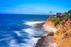Cliffside home overlooking ocean. A scenic shot of a cliffside home that overlooks the rugged ocean.  Image was created in camera using a slow shutter speed to Stock Images