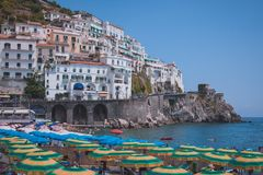 Cliffside houses and beach umbrellas in Amalfi Town, Italy. Cliffside houses and beach umbrellas along Amalfi Coast in Amalfi Town, Salerno Italy Stock Photography