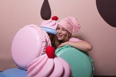 Clignant de l'oeil la femme blonde utilisant le chapeau rose et le T-shirt ayant l'amusement avec de grands macarons et petits gâ image libre de droits