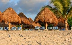 Clima tempestuoso Playa arenosa tropical con las palmas, los paraguas de la paja y los sillones rayados Foto de archivo libre de regalías