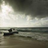Clima tempestuoso y barco de pesca trenzado en una playa Fotografía de archivo libre de regalías