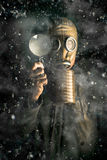 Climate Change. Scientist wearing a gas mask and holding a magnifying glass in a snow storm conducting research into the effects of gases, pollutants and carbon Royalty Free Stock Images