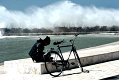 Climate change. Civitavecchia Rome Italy Bad weather climates A boy with his bicycle while reading a book between a strong wind and a swamp on the coast coast royalty free stock photos