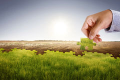Climate change concept. Businessman hand assemble puzzle to build new world with fresh environment. Climate change concept stock images