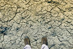 Climate change concept, man in dirty shoes stands on dried crack Royalty Free Stock Photo