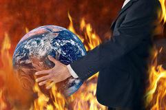 Climate Change Earth Fire Fires Business. A  businessman holding a burning world globe