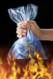 Climate Change Plastic Bag. The earth in a plastic bag over a fire. Plastics are a major source of pollution filling our oceans and waterways becoming micro