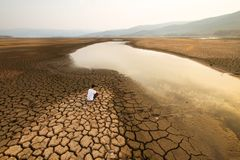 Climate change and Global warming Environmental concept. Sad Young man sit on cracked earth near drying lake in the summer. Climate change and Drought impact stock images