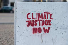 Climate justice now. Sign painted on concrete wall Stock Photos