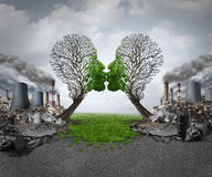 Climate Recovery. And environmental  renewal as two empty trees shaped as human heads kissing and reviving new green growth  out of a polluted industrial Royalty Free Stock Photo