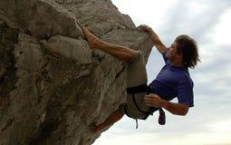 The climb. Man climbing a steep rock with overhang Stock Photos