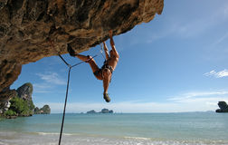Climb on!. Adult climbing hard overhanging wall in Krabi, Thailand stock images