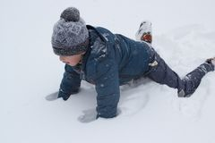 Climb on the feet of the snow. The boy fell on his stomach in the snow and stands on his feet Royalty Free Stock Images