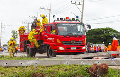 Climb the fire department. PHICHIT THAILAND-AUGUST 7:Officer or firefighter was climbing down from a fire engine red, with power poles toppled barricades road royalty free stock photo
