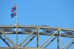 Adventurous daredevil climbing Sydney Harbour Bridge with Australia & NSW flags and clear blue sky in the background
