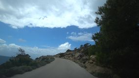 Climb to the mountains by car along a steep narrow road along the sea, view from the car