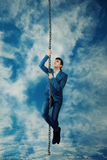 Climb to the sky. Afraid Businessman climbing on a chain rope try to reach the sky. Business success, opportunity and risk concept Stock Photos