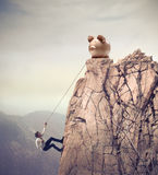 Climb to Success. Young businessman scaling a rock to reach a large piggy Royalty Free Stock Images