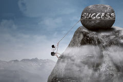 Climb to Success. Businesswoman climbing steep mountain hanging on rope Royalty Free Stock Photo