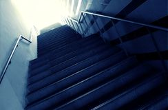 Going towards the light. A concept photograph showing a flight of steps leading from the darkness into the bright light.  Positive conceptual image for walking Stock Photo