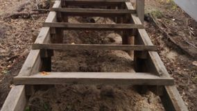 Climb up the narrow wooden stairs in the park in autumn. close-up wooden steps lead up