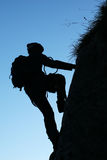Climber. Silhouette of a climber on blue background Stock Image