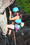 A climber. A female climber rappelling outdoor on the rocky background Royalty Free Stock Images