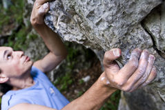 Climber. Rock climber working for the top of a rocky steep wall Stock Image