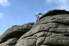 Climber. A rock climber reaching the top Stock Image