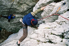 Climber. Man climbing a steep rock with overhang stock image