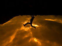 The climber. Silhouette man climbing on orange cloudy sunset royalty free stock image