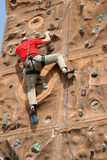 Climber in action. Climber climbing up the wall Stock Photo