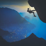 Climber against sunrise above the city. Instagram stylisation Stock Images